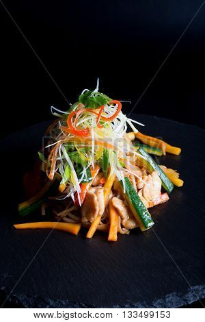 Asian fried noodles with meat on a black background