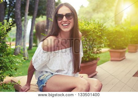 Young smiling beautiful woman in sunglasses is sitting on a cushion in sunny green yard