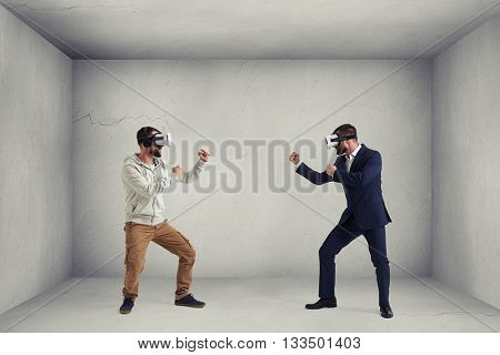 Two men, one in casual clothes, another in dark business suit, are wearing virtual reality glasses and standing in fighting poses ready to start their combat in virtual reality in room