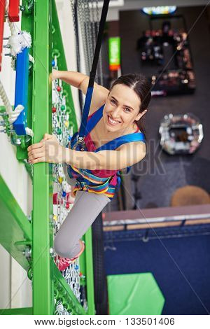 Young smiling sportswoman in safety harness is climbing high on the wall in indoor sport center