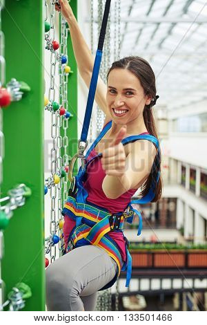 Sportswoman in safety equipment is smiling and making a thumb up gesture while climbing on the wall with chains in indoor rock-climbing center