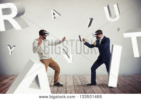 Two men, one in casual clothes, another in dark business suit, are wearing virtual reality glasses and standing in fighting poses ready to start their combat