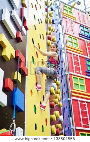 A smiling young woman in safety harness is climbing on a high rock-climbing wall in gym