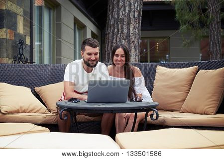 Young joyful smiling couple is sitting on the couch with cushions on spacious terrace in the yard and watching something in their laptop