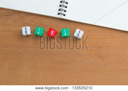 Color fraction dices blank white notebook on wooden desk with copyspace for text