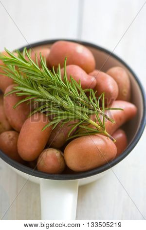 Potatoes with rosemary twig in a vintage enamel skillet