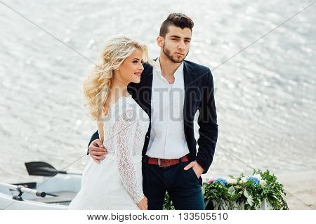 Bride And Groom Walking Near The Boat At River
