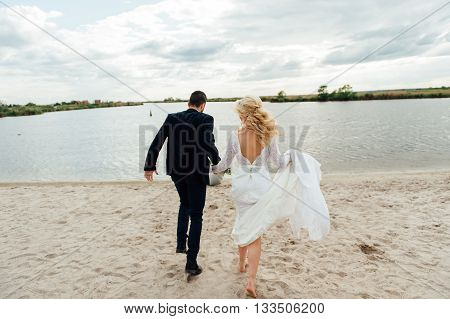 Bride And Groom Walking At The River