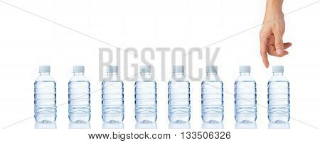 Man's hand reaching down for a clean and clear bottle of water from a line of eight water bottles isolated white background