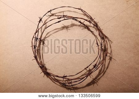 Barbed wire circle isolated on brown background