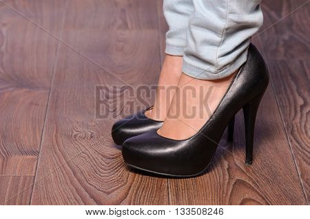 Leggy girl in black shoes with high heels on the wooden floor