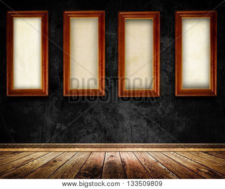 Old black concrete wallfour wooden frames with canvas and old wooden floor with decorative plinth.