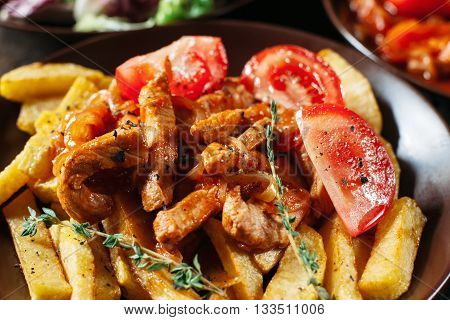 Fried potato with meat and tomato close-up. Serving of clay brown plate with fried potato with meat . Served table with food, focus on portion of fried potato with meat and tomato.