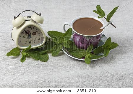 Cup of coffee with a spoon on the saucer, and an alarm clock on gray linen table cloth, decorated with green mint leaves.