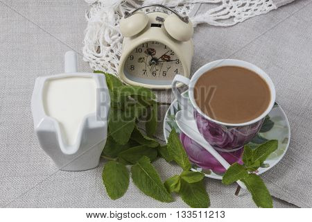 Cup of coffee on a saucer with a spoon, a jar of cream and an alarm clock on gray linen table cloth, decorated with green mint leaves.