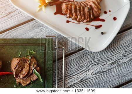Plate and tray with meat. Cooked meat with sauce. Veal medallions and duck steak. Finest dishes of restaurant menu.