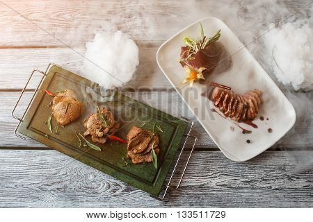 Cooked meat with herbs. Plates with slices of meat. Veal medallions with duck steak. Dishes served with dry ice.