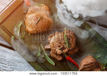 Pieces of meat with pepper. Cooked meat on green tray. Tasty veal medallions with spices. Smoke from dry ice.