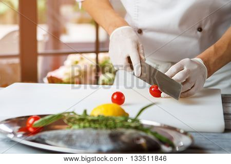 Hands with knife cut tomato. Small tomatoes on cooking board. Restaurant chef prepares food. Juicy cherry tomatoes.