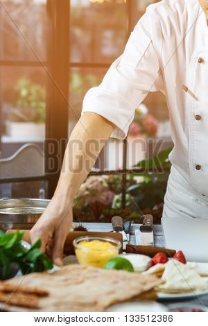 Hand touching plate with strawberries. Sweet food ingredients. Chef starts cooking dessert. Confectioner busy in the kitchen.