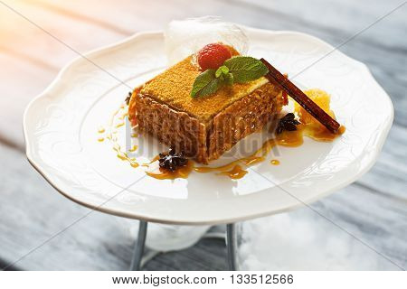 Cinnamon stick and cake. Raspberry and small mint leaves. Traditional european dessert. Decorated honey cake on plate.