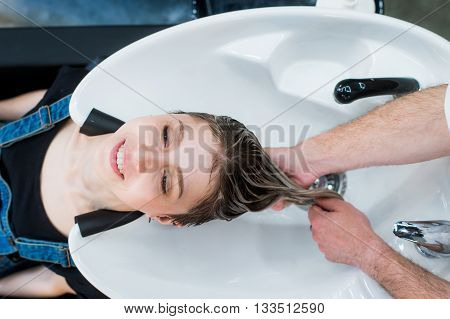Hairdresser's hands washing woman's hair in salon. Top view
