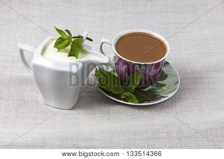 Cup of coffee on a saucer and a jar of cream, decorated with mint leaves on a background of gray fabric from  flax.
