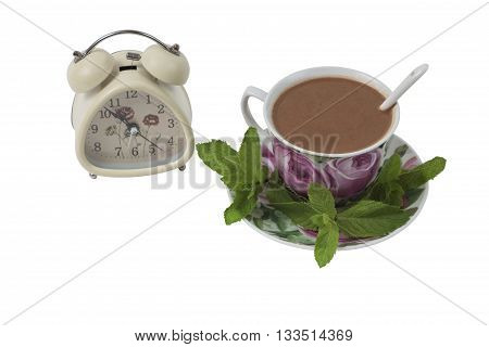 Isolated cup of coffee with a spoon on the saucer next to the clock on a white background.