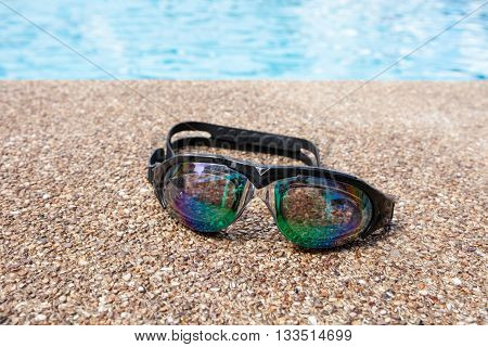 Glasses For Swimming On A Cement Floor With Small Stone Near Swimming Pool