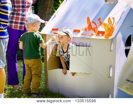 Zaporizhia/Ukraine- June 5, 2016: small boy, having fun,  looking from the window of house on painting cardboard houses activity during charity family festival organized in regions with most quantity of refugees from Donetsk area, occasioned with Internat