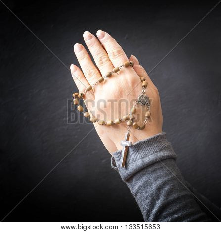 female hands praying with rosary over dark background