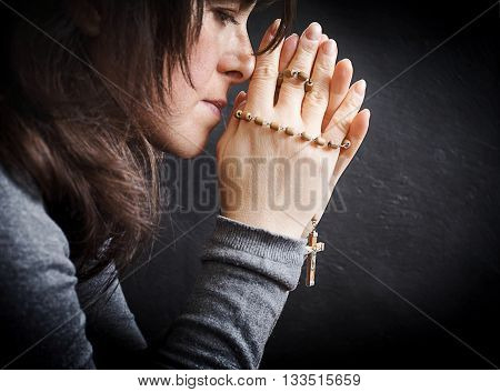 Concentrated Woman Praying With Rosary