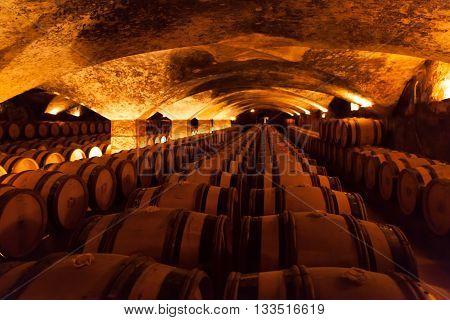 underground wine barrel storage cellar full of wine being aged to maturity