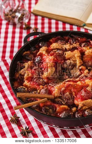 Light summer plums skillet cake on a red tablecloth in a cage with a cookbook and spices
