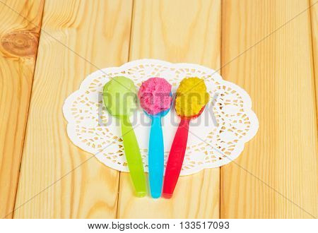 Various types baby puree in plastic spoon on a background of light wood.