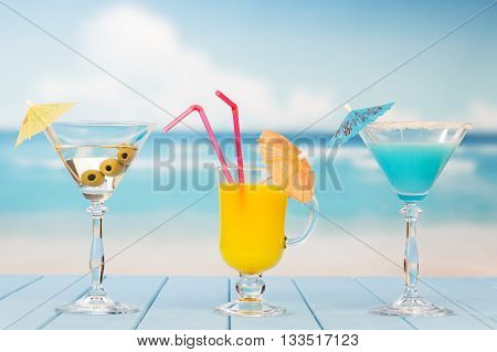 Martini glass with olives, drink and juice on the background of the sea.