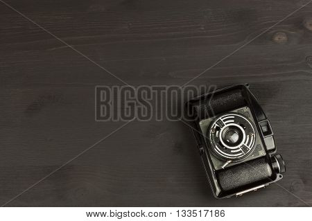 Old camera on a black wooden background. The camera of the past. Advertising for the sale of the camera. For roll film camera. Equipment artistic photographer.