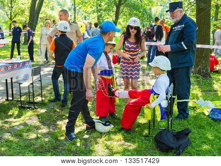 Zaporizhia/Ukraine- June 5, 2016: Parents and their sons, wearing traditional Ukrainian clothes, practicing premedical first aid at  workshop organized in regions with most quantity of refugees from Donetsk area, occasioned with International Children`s D