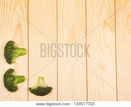 Fresh broccoli close-up on a background of light wood.