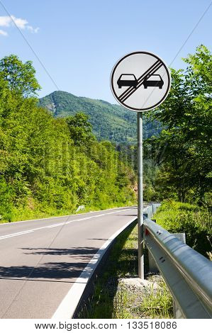 End of overtaking prohibition road traffic sign on a signpost at the side of an empty mountainous road