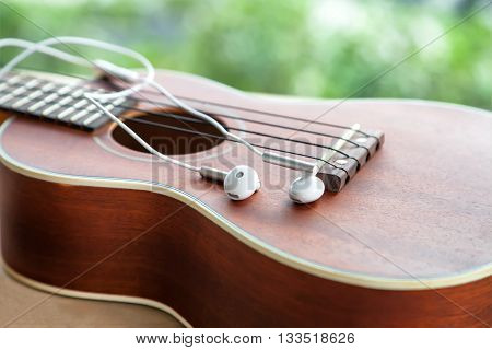 close-up of earphone with ukulele guitar on wooden table in the garden