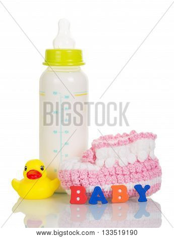 Bottle with milk mixture, booties, rubber duck, and the inscription BABY isolated on white background.