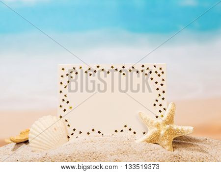 Blank white card, starfish and shell in the sand against the sea.
