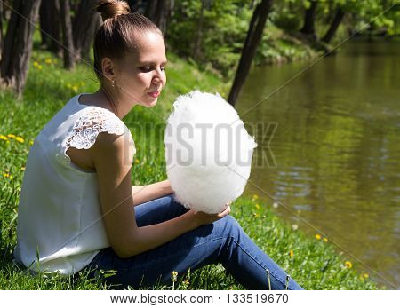 Beautiful girl holding a cotton candy in the park