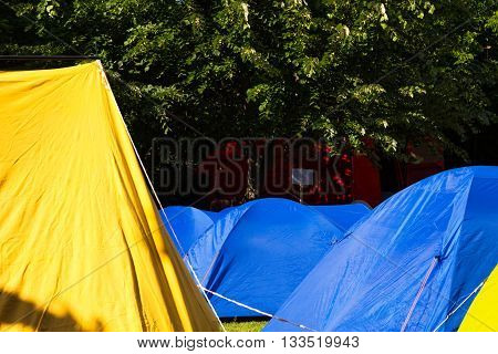 Group of colorful yellow and blue tents at a campsite pitched in front of leafy green trees in a concept of an active outdoors lifestyle