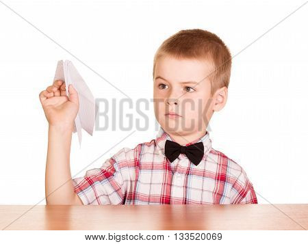 Sitting at the table pretty boy with paper plane in the hand on a white background.