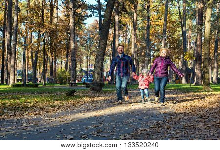 Family of Three People Young Man Woman Baby Girl Laughing Running on Park Running Track Holding Hands Autumnal Color Trees and Leafs