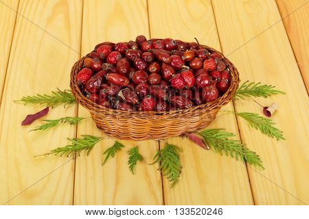 Dried rosehip berries in a wicker basket isolated on white background.