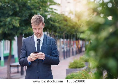 Young businessman sending a text message on a cellphone while walking in the city