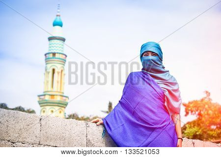 Young muslim woman standing with traditional islamic clothing - Portrait of asian girl with veiled face on minarets background - Concept of world religions - Soft vintage filter with sunset lights